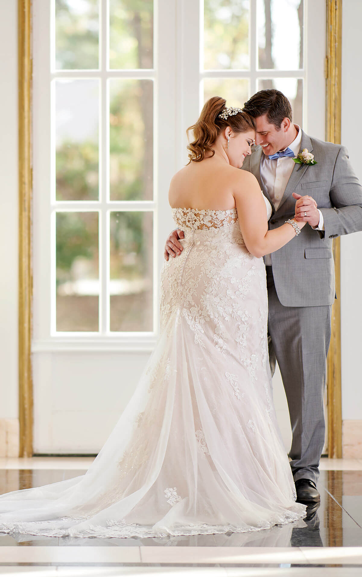plus sized bride wearing gown with lace back and flared skirt